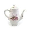 Vintage koffiepot met roze bloemen en een zittende yoga instructrice